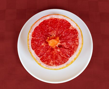 A half of a grapefruit on a white disk and red