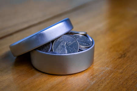 Open silver container filled with coins on a wooden table and an unfocused background Stock Photo