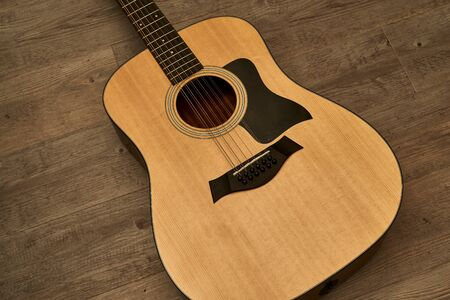 12-string acoustic guitar body on a brown wooden floor
