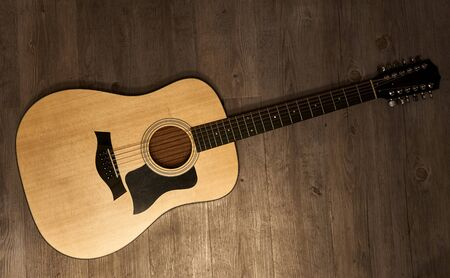 Full 12-string acoustic guitar on a brown wooden floor