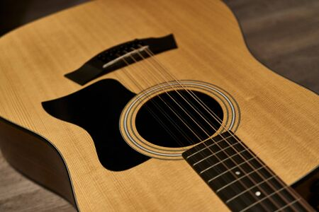 Detail of the sound hole of a 12-string acoustic guitar with black pick guard on a brown wooden floor