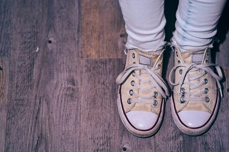 Girl standing on a brown wooden floor with worn out yellow sneakers