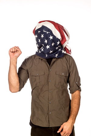 Man with American flag over his head as a hood being rebellious with raised fist.