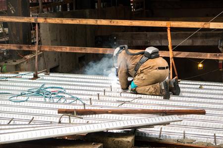 Un hombre se arrodilla sobre la soldadura de chapa mientras usa un protector, casco, máscara y respirador haciendo su trabajo en un sitio de trabajo de construcción. Foto de archivo