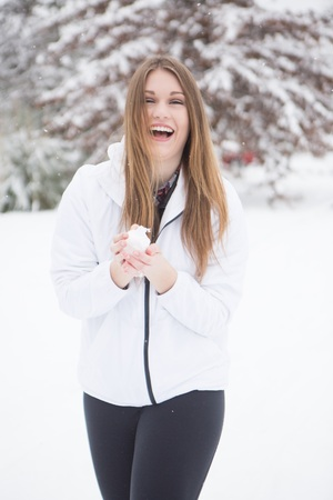 Young adult woman, making and throwing snowball during a winter snow storm. Stock Photo