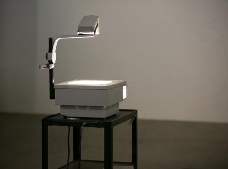Um projetor aéreo do vintage senta-se em um carro do rolo que ilumina uma parede pronta para mostrar transparências aéreas da projeção. Os retroprojetores eram frequentemente usados na escola e nos negócios antes da projeção digital.