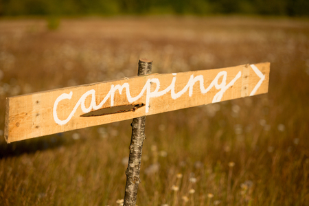 A rustic sign points to a camping area in a dry yellow grass field on a bright summer day.