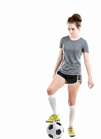 Athletic teen girl playing soccer with ball, shin guards and soccer cleats.