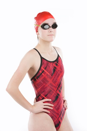 Pretty teen girl wearing red swimsuit, with swim goggles wearing swim cap.