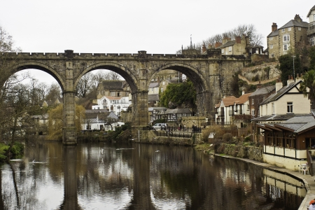 Historical stone viaduct bridge with arches reflected in the still water of the river at Knaresborough, England Stock Photo