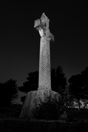Low angle black and white image of a large stone Celtic cross on a plinth outlined against darkness Stock Photo
