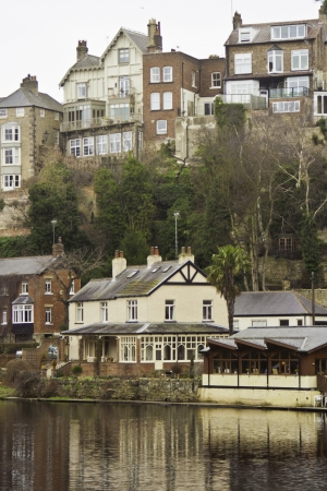 Town of Knaresborough, England, with its quiant historical houses reflected in the water of the river below