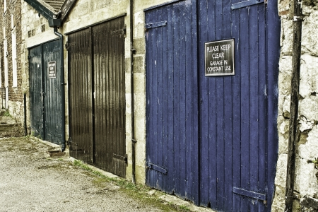 Row of grungy painted garage doors in an urban environmnet with a Please keep clear sign on one