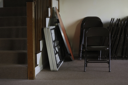 Folding tables and chairs stacked at the bottom of a stairwell in an entertainment venue, meeting hall or school Stock Photo - 17337718