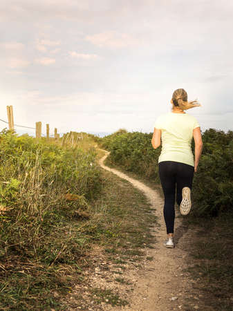 Woman running along a path at sunset Stock Photo