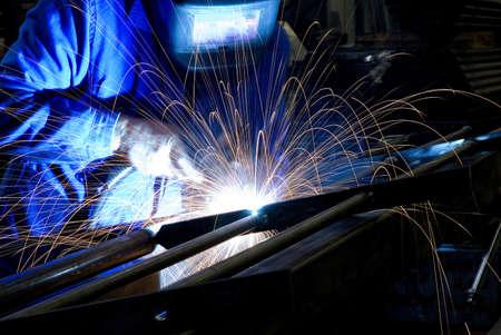 machining: Welder in action. Sparks of light.
