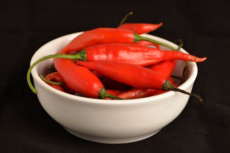 hot chili pepper in white ceramic pot with black background
