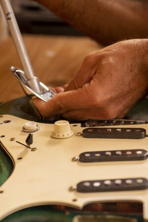 luthier working on repairing a guitar Stock Photo