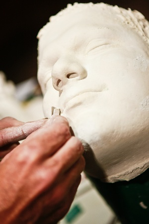 sculpt: Artist working on plaster cast of a human face.  Stock Photo