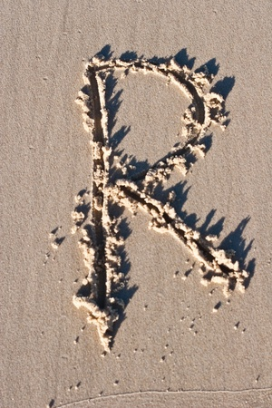 Letter R drawn in the sand.  Stock Photo - 8816488