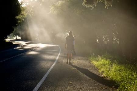 Woman roaming down a misty road.