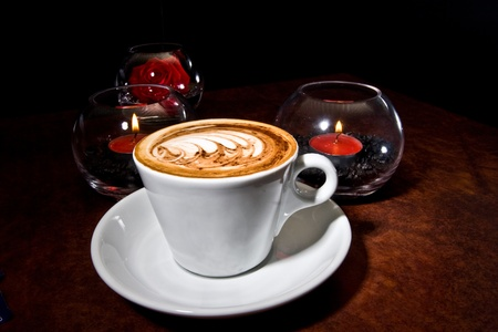 Elegent mug of cappucino surrounded by candles.  Stock Photo