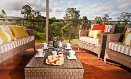 Comfortable outdoor wicker furniture with striped cushions on a wooden deck overlooking a garden with a low table set for tea and cookies