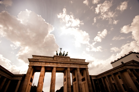 Brandenberg Gate in Berlin with the Quadriga statue with its four horses silhouetted against a dramatic sky Stock Photo