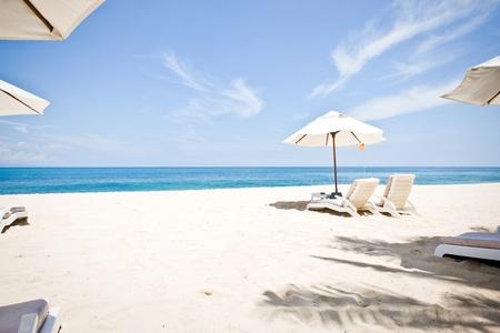 arena blanca: Blanca arena del oc�ano y sombrillas con sillas de playa