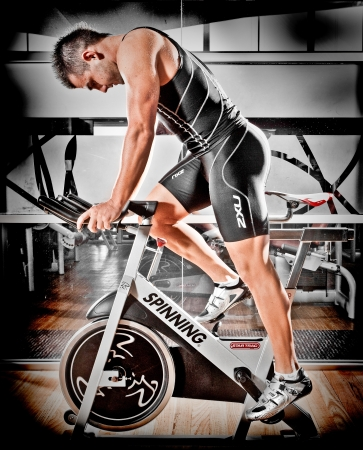 spinning: Strong fit athletic man training in a gym on a spinning bike in a health and fitness concept, sideways profile