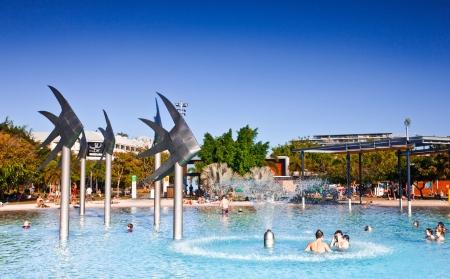 ケアンズ、クイーンズランド州、オーストラリアのスイミング ・ ラグーンでの魚の彫刻の中で泳ぐ人々