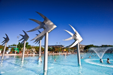 frolicking: Swimming lagoon and steel Fish Sculpture in Cairns, Australia with people enjoying the summer sun frolicking in the water