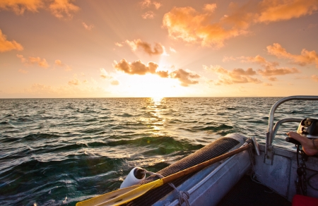 Spectacular orange sunset over the ocean viewed from a rigid inflatable in mid ocean photo