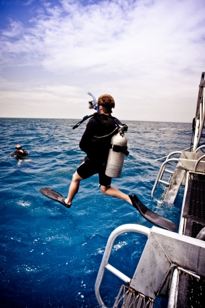 Diver leaping into the sea off a boat with his aqualung and diving gear