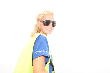 Beautiful young blond female member of a dive team wearing a fluorescent high visibility jacket and sunglasses turning to smile at the camera photo
