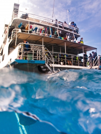 View from the water of the back of a tourist dive boat with people on the decks in mid ocean