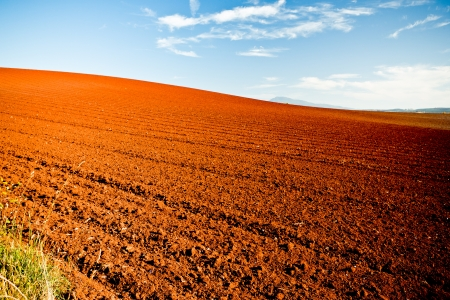 Red earth in newly turned and ploughed agricultural fields under a blue summer sky in a beautiful Australian landscape photo