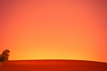 Background image of a vivid orange sunset over newly ploughed agricultural fields left fallow awaiting a crop in farmland, with copyspace photo