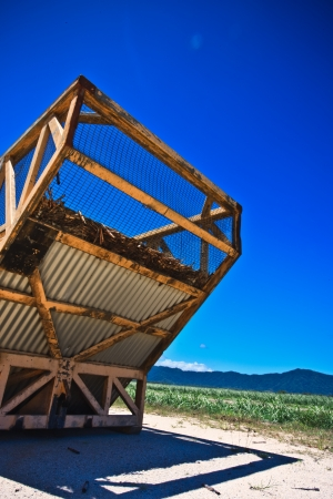 storage bin: Agricultural storage bin of corrugated iron and wire mesh standing alongside a crop growing in a field in Queensland Australia under a blue sunny summer sky
