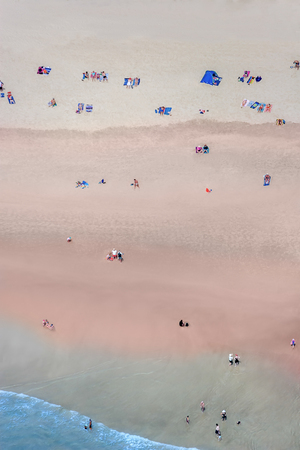 distributed: Some people on a beach photographed from high above on a bright day