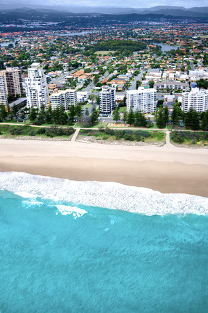 surfers paradise: Empty beach bathed by a deep turquoise color sea located just in front of a big city, surfers paradise