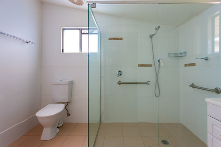 contemporaneous: Simple bathroom with a big shower cabin with glass walls and support handles