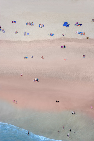 Some people on a beach photographed from high above on a bright day
