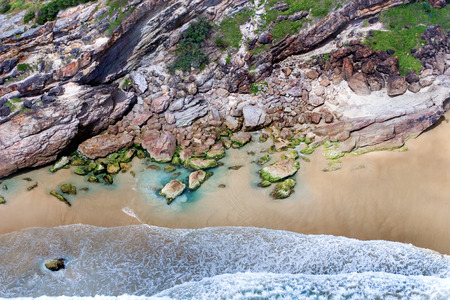 astonishing: Astonishing shot of a rocky coast with a small beach being washed by sea water Stock Photo