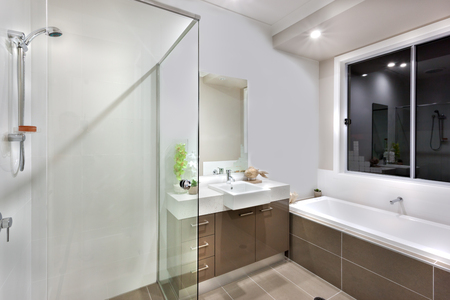 git: The water tub is long and white. there is a window over it. the bath room git a silver color shower attached to the white wall. there are fancy pants with a wooden fish under the mirror and near to the sink with tap, the lights are  turned on Stock Photo