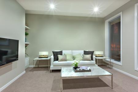 窓の正面の壁に黒い色のテレビ。ソファは明るい色の壁に白い、両サイドのランプで 2 つのテーブルがあります。テーブルは、カーペットの床では 写真素材