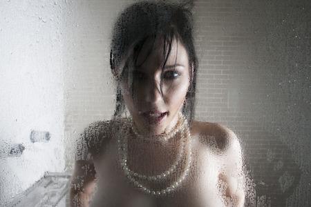 jeune femme nue: Sexy femme seins nus dans une douche portant un collier de perles et debout derrière une porte en verre