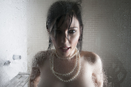 wet breast: Sexy topless woman in a shower wearing a pearl necklace and standing behind a glass door Stock Photo