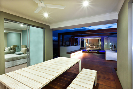 wooden  ceiling: A wooden table and a wooden bench made using rectangle shaped bars on a wooden floor in the luxury house at night environment. The ceiling has two flshing lights of this area. the bed room lighting can be seen throught glass door. The lights turned on und Stock Photo