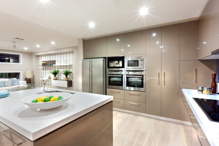 The wall cabinets with the overns and the refrigerator in front of the  white countertop with fruit dish and faucet next to the black stove illuminated using lights, there is a living room next to the kitchen, the reflection of the lights can be seen thro Banco de Imagens